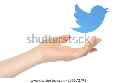 KIEV, UKRAINE - JANUARY 05, 2015: Hand with Twitter bird printed on paper flying away.Twitter is an online social networking service that enables users to send and read short messages. - stock photo