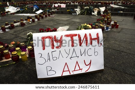 "KIEV, UKRAINE - January 22, 2015: Homemade banner with the words ""Putin get lost in hell"" against the background of lit lamps. At the Independence Square  honored memory of those killed in Mariupol - stock photo"