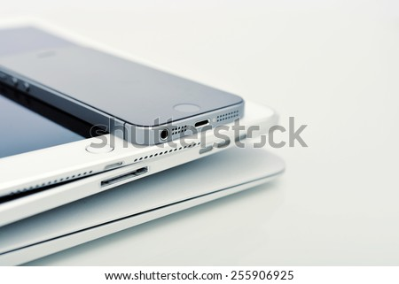 KIEV, UKRAINE - JANUARY 29, 2015: Pile of Apple iPhone 5s, iPad Air 2 and MacBook Air . Apple Inc. is an American multinational corporation that designs, develops, and sells consumer electronics.