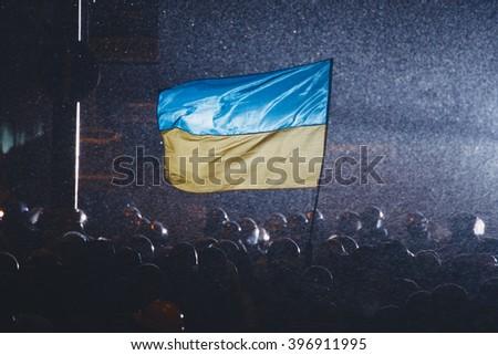 Kiev, Ukraine - 21 January, 2014: Ukrainian flag on the barricade at Hrushevskogo street in Kiev. One of the protester raised flag of Ukraine. During anti-government protests in Kiev - stock photo