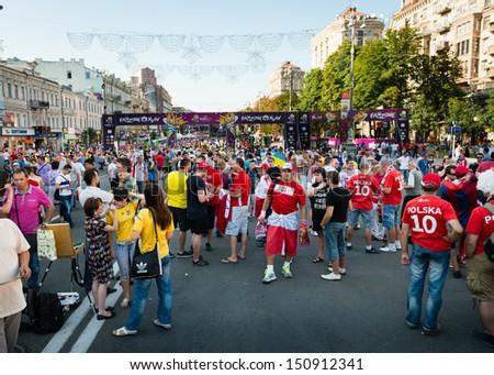 KIEV, UKRAINE - JUL 1: Football fans walk on the central fun zone before EURO 2012 final match Spain vs. Italy on July 1, 2012 in Kiev, Ukraine - stock photo