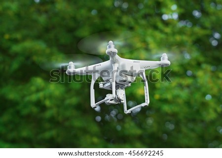 KIEV, UKRAINE - JULY 14, 2016: Closeup of a white drone quadrocopter flying over the trees in the park. - stock photo