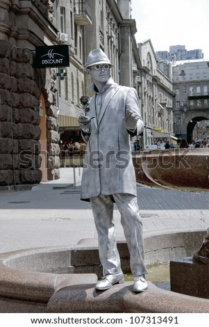 KIEV, UKRAINE - JUNE 30: An unidentified busking mime performs on Khreshchatyk street in Kiev, Ukraine on June 30, 2012. Living silver statue is the entertainment for the tourists. - stock photo