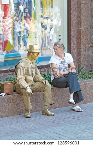 KIEV, UKRAINE - JUNE 30: An unidentified passerby chats with an unidentified busking mime performing on Khreshchatyk street in Kiev, Ukraine on June 30, 2012. Living statue is tourists entertainment. - stock photo
