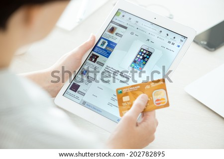 KIEV, UKRAINE - JUNE 27, 2014: Person holding a credit card and trying to buy a new Apple iPhone 5 with eBay application on a brand new Apple iPad Air. eBay is the online auction and shopping website. - stock photo
