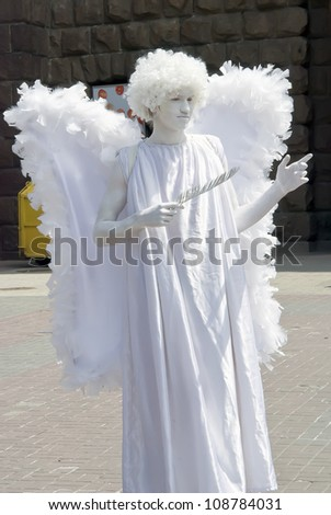 KIEV, UKRAINE - JUNE 30: Unidentified busking mime in the image of an angel performing on Khreshchatyk street in Kiev, Ukraine on June 30, 2012. Living statues are the entertainment for the tourists. - stock photo