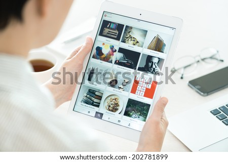 KIEV, UKRAINE - JUNE 27, 2014: Woman looking on Pinterest application boards on modern white Apple iPad Air, which is designed and developed by Apple inc. and was released on November 1, 2013. - stock photo