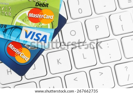 KIEV, UKRAINE - MARCH 21, 2015: Cards Visa and MasterCard are placed on white keyboard background. Online shopping, banking or paying concept. - stock photo