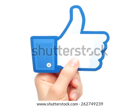 KIEV, UKRAINE - MARCH 7, 2015: Hand holds facebook thumbs up sign printed on paper on white background. Facebook is a well-known social networking service. - stock photo