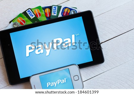 KIEV, UKRAINE - March 29: PayPal payment system logo on tablet and smarphone with plastic payment cards, Visa and MasterCard, in Kiev, Ukraine, on March 29, 2014. - stock photo