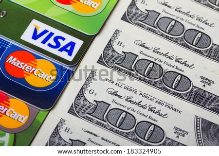 KIEV, UKRAINE - March 22: Pile of credit cards, Visa and MasterCard, credit, debit and electronic with US dollar bills, in Kiev, Ukraine, on March 22, 2014. - stock photo