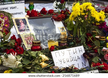 "KIEV, UKRAINE - MARCH1, 2015: Portrait of Boris Nemtsov, surrounded by flowers and lamps, in the foreground a banner with the inscription ""Putin - murderer""  - stock photo"