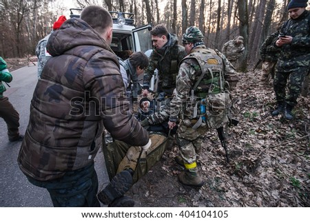 """KIEV,UKRAINE - March 26 : Volunteers carry injured soldier to ambulance during demonstration first aid on military training for civilians """"RUH 100.Tryzub""""  in Kiev,Ukraine on March 26,2016. - stock photo"""