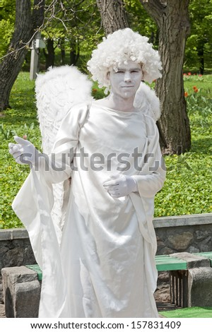 KIEV, UKRAINE - MAY 01: An unidentified busking mime in the image of angel performing on Spivoche Pole park in Kiev, Ukraine on May 01, 2013. Living statue is the usual entertainment for the tourists. - stock photo