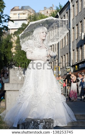 KIEV, UKRAINE - MAY 11: An unidentified busking mime with parasol performs on Khreshchatyk street in Kiev, Ukraine on May 11, 2013. Living statues are the entertainment for the tourists. - stock photo