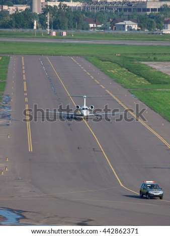 "Kiev, Ukraine - May 17, 2012: Business jet is taxiing after a ""Follow Me"" car"