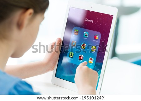 KIEV, UKRAINE - MAY 21, 2014: Little girl looking on a brand new Apple iPad Air with various game applications on a screen. Apple iPad Air developed by Apple inc. and was released on November 1, 2013. - stock photo