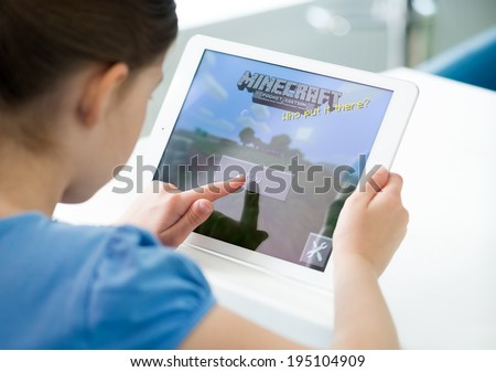 KIEV, UKRAINE - MAY 21, 2014: Little girl start playing Minecraft game on brand new Apple iPad Air. Minecraft is very popular game for mobile devices, was released for iOS version on November 17, 2011 - stock photo