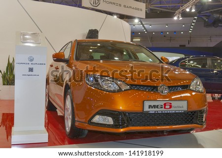 KIEV, UKRAINE - MAY 29: Visitors visit Morris Garages MG6 hatchback car model on display of SIA' 2013 Kyiv International Motor Show in International Exhibition Centre on May 29, 2013 in Kiev, Ukraine. - stock photo