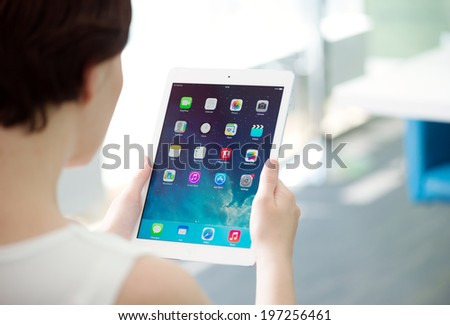 KIEV, UKRAINE - MAY 21, 2014: Woman holding brand new white Apple iPad Air, the most advanced digital tablet in part of the iPad line. Developed by Apple inc. and was released on November 1, 2013. - stock photo