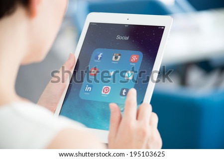 KIEV, UKRAINE - MAY 21, 2014: Woman looking on social media applications on modern white Apple iPad Air, which is designed and developed by Apple inc. and was released on November 1, 2013. - stock photo