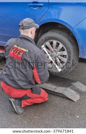 KIEV, UKRAINE - NOVEMBER 24, 2015: Tip-Top Service worker provide outdoor seasonal Pirelli winter tire changing on Subaru Impreza car. TTS is a Ukrainian network of tire fitting centers and car washes - stock photo
