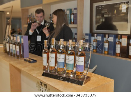 KIEV, UKRAINE - NOVEMBER 21, 2015: Unrecognized presenters work on The Macallan Single Malt Scotch Whisky distillery booth at 1st Ukrainian Whisky Dram Festival in Parkovy Exhibition Center. - stock photo