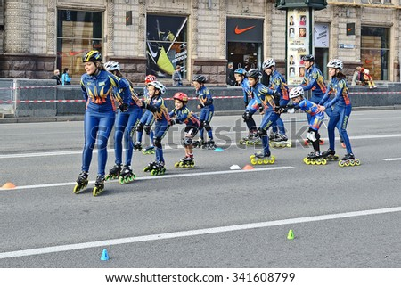 KIEV, UKRAINE - OCTOBER 21, 2012: Town sport competition between schoolchildren, the race on roller skates. Heat of Twin-row group schoolchildren with nice young girl-teacher ahead.