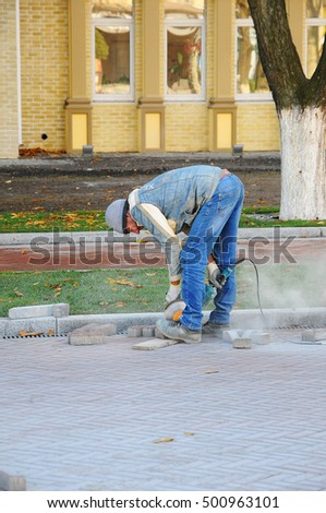 KIEV, UKRAINE - SEPTEMBER 10, 2016: Cutting concrete paving stabs or metal using a cut-off saw. Work on laying of paving slabs