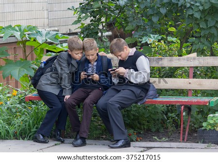 Kiev, Ukraine - September 10, 2015: Students after class sitting on the bench played with the help of smartphones