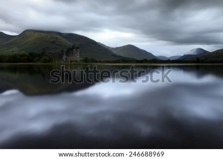 Kilchurn Castle in Scotland with a dark weather  - stock photo