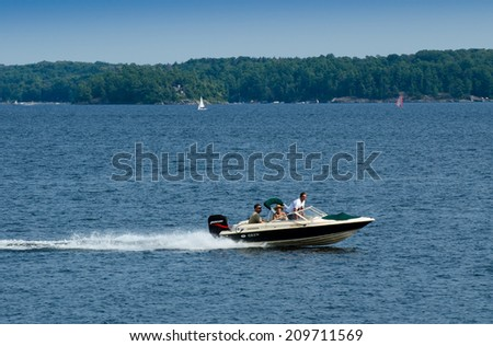 KILLBEAR PROVINCIAL PARK - AUGUST 2, 2014: Speeding powerboat, sailboat, and a windsurf board on calm water in Killbear Provincial Park, one of the largest recreational parks  in Ontario. - stock photo