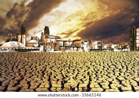 Killed nature. Cracked dried ground in front of an industrial plant. - stock photo