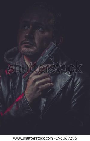 Killer, Assassin, man with black coat and gun - stock photo