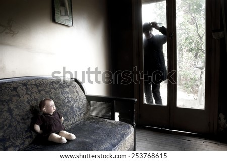 Killer holding a knife. Spooky shadow of a man with knife in his hand looking through the dirty glass of the backdoor of a old house - stock photo