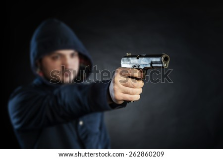 killer holding gun isolated on a black background - stock photo