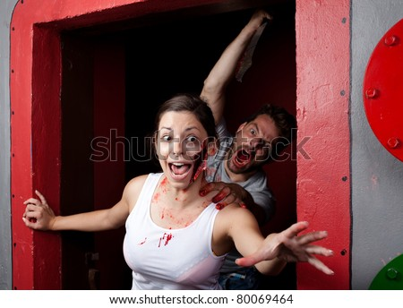 Killer with a machete in his hand, chasing young woman with a bi - stock photo