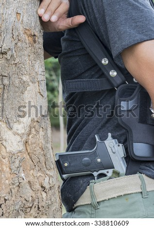 Killer with gun behind the tree close on nature background .