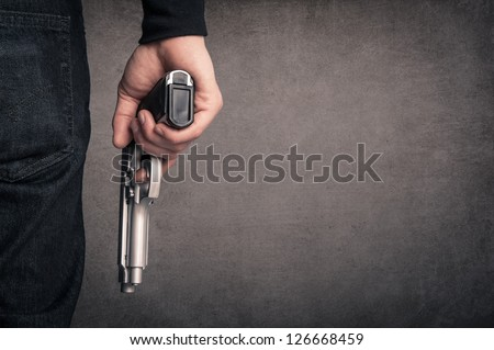 Killer with gun close up over grunge background with copyspace. - stock photo