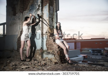 Killer woman in bloody bandages bandaged with a katana in his hands resting sneaks to a girl who looks at the sunset sky. The shadow on the wall of a building destroyed. Murderer and the victim - stock photo