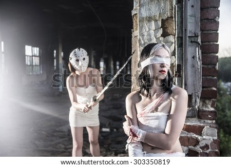 Killer woman in bloody bandages bandaged with a katana in his hands resting sneaks to a girl with closed eyes. Light on floor of a building destroyed. Murderer and the victim Facial Mask - stock photo