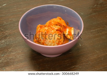 Kimchi in a bowl on a wooden table - stock photo