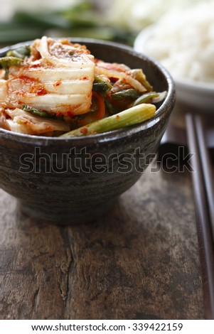 kimchi of chinese cabbage and spring onion with cooked rice place on old wood background. - stock photo