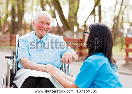 Kind doctor, nurse outdoors taking care of an ill elderly woman in wheelchair. - stock photo