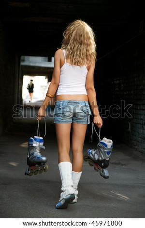 Kind from a back in moving of the young sports girl with the rollers in the dark tunnel - stock photo