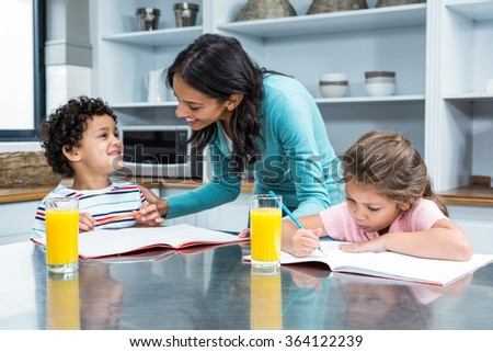 Kind mother helping her children doing homework in kitchen - stock photo