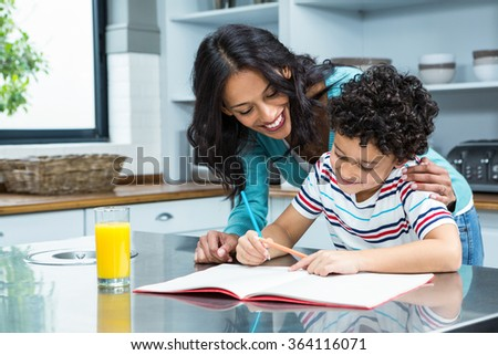 Kind mother helping her son doing homework in kitchen