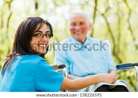 Kind nurse taking care of elderly lady patient in wheelchair. - stock photo