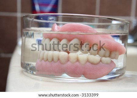 Kind of scary, isn´t it? :-)... an artificial denture of a senior in a glass of water in the bathroom. Shallow depth of field. Focus on the teeth. - stock photo