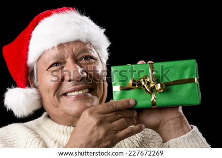 Kind old gentleman with red Santa Claus cap is showcasing a green wrapped Christmas present. Affirmative smile, white teeth and sparkling eyes. Isolated on black. Reminder for gift-giving occasion. - stock photo